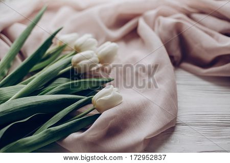 Stylish White Tulips On Beige Soft Fabric And Rustic Wooden Table Background. Hello Spring. Soft Lig
