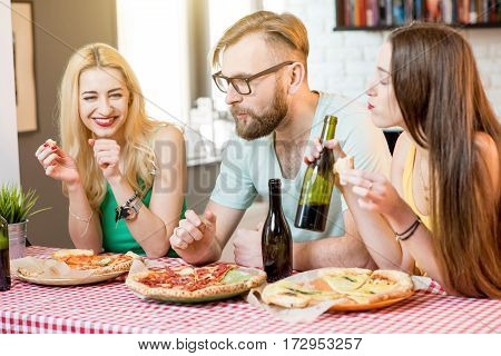 Young friends dressed casually in colorful t-shirts having lunch with pizza and beer at home