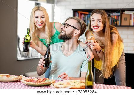 Young friends dressed casually in colorful t-shirts having fun eating pizza and drinking beer at home