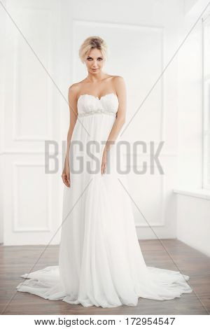 Classical young gourgeous bride. Studio interior fashion shot of fashion model in wedding dress in white room. Blonde woman in full lenght looking at camera.
