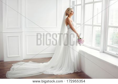 Classical young gourgeous bride. Studio interior fashion shot of fashion model in wedding dress with bouquet of flowers in white room with big window. Blonde woman portait with profeshional make-up and hairstyle.