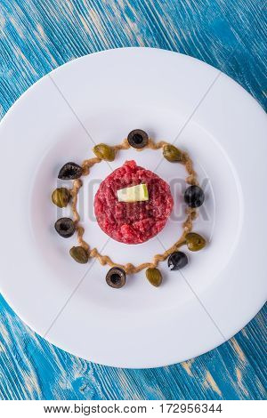 Top View On Single Portion Of Beef Tartar Steak On White Plate