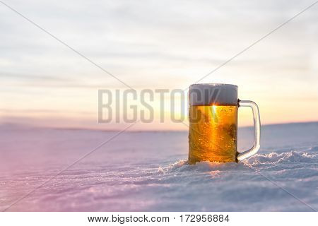 Mug of cold beer on the snow. Close up view.