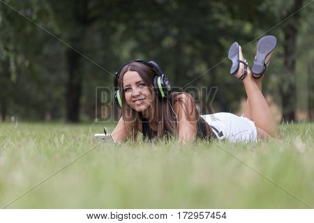 Beautiful young woman listening to music in nature Selective focus and small depth of field lens flare