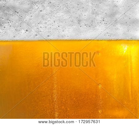 Background beer with foam and bubbles .The texture of the glass with beer. Droplets on freshly poured beer. Mug of cold beer close-up. Copy-space for advertising.