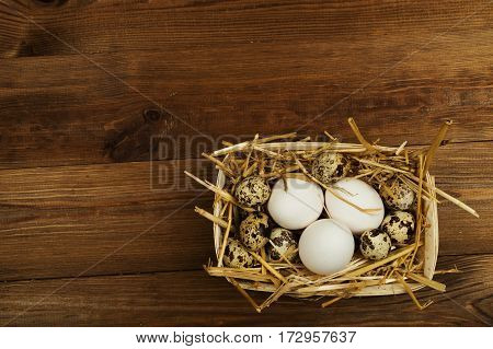 Chicken and quail eggs on the wooden table. Easter background.