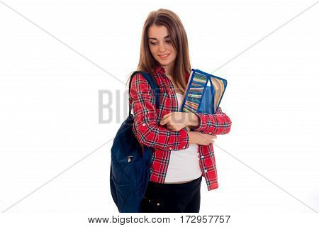 tired stylish student girl with backpack on her shoulders and folder for notebooks in her hands posing isolated on white