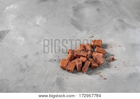 Milk aerated chocolate is on the gray concrete background. Pieces of chocolate are chaotic and sloppy in composition. Around the broken-up chocolate bars are chocolate chips.