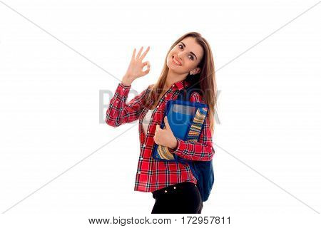 cheerful stylish student girl with backpack on her shoulders and folder for notebooks in her hands posing and showing OK isolated on white