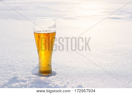 Mug of cold beer in the snow at sunset. Beautiful winter background. Outdoor recreation. Advertising of alcoholic beverage. Booze and holidays.