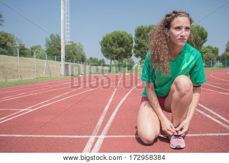 female athlete on running track ready to start