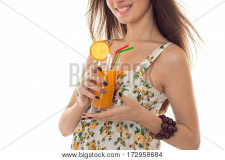 close up of cheerful brunette woman in sarafan with floral patter drinks fresh orange cocktail and smiling isolated on white