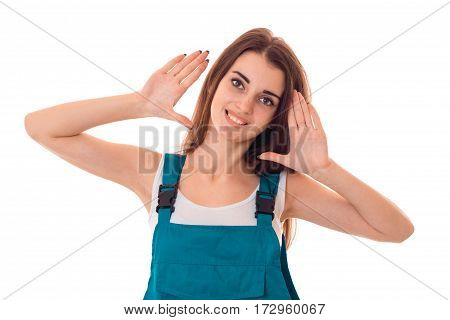 young cheerful brunette woman in uniform makes renovationand smiling on camera isolated on white