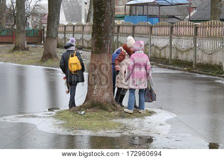 group of happy vivid school girls with bags play on island in center of big frozen puddle