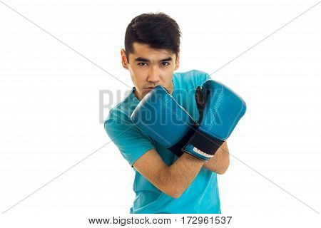 Handsome young sports man in blue gloves and uniform practicing boxing isolated on white