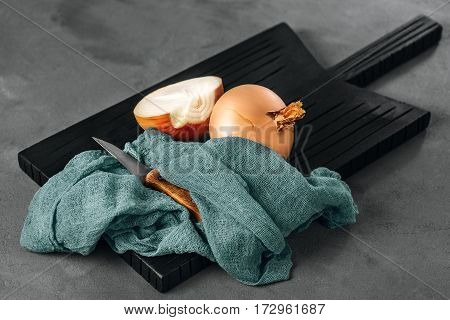 Onions is located on a black kitchen board. Half of the onion is cut with a knife with a wooden handle. The composition is decorated with a cotton cloth or runner. Dark background.