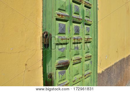 Yellow wall with a green door locked with a padlock picture from Tenerife Spain.