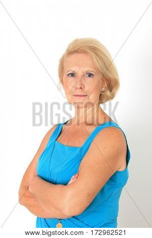 Portrait of a beautiful seventy year old lady with a serious expression. Studio shot, isolated on white.