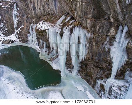 Aerial Photos. Large icicles hanging from a frozen cliff of a mountain stream.