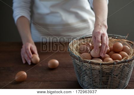 Woman taking fresh farm chicken eggs from metal, wire basket