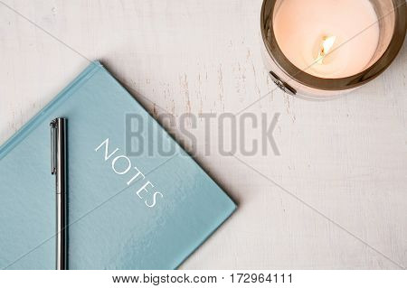 Notebook and Candle on White Wooden Table