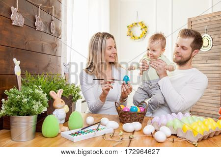 Easter Concept. Happy Mother And Father Preparing Home Decoration With Their Child For Easter Holida