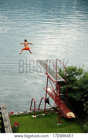 HALLSTADT, AUSTRIA, JULY 07, 2006: Courageous boy jumps from a diving board into the lake
