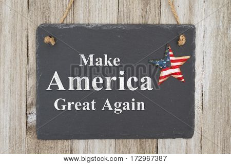 A rustic patriotic American message A retro chalkboard with a vintage USA star hanging on weathered wood background with text Make America Great Agian