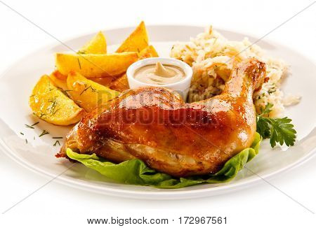 Grilled chicken leg with chips and vegetables on white background