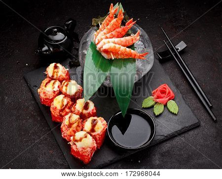 Japanese Cuisine. Baked (hot) Sushi Roll And Shrimp Skewers On A Stone Plate Over Black Concrete Bac