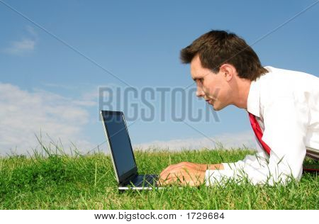Portrait of a young businessman working on laptop outdoors poster
