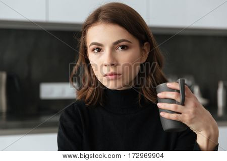 Picture of young beautiful lady standing with cup of coffee at kitchen. Looking at camera.