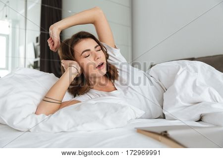 Photo of young pretty woman dressed in white t-shirt lies in bed at home indoors. Stretching and yawning.