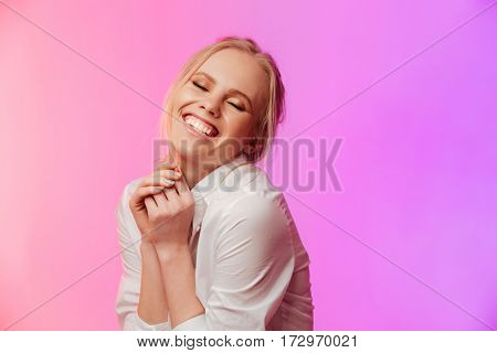 Image of young happy lady dressed in white shirt standing and posing over pink background. Eyes closed.
