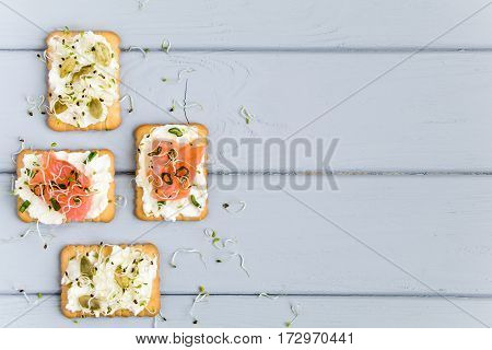Tasty square crackers with cream cheese salmon pumpkin seeds and micro greens. Appetizers on a plate on grey table. Healthy snacks top view flat lay