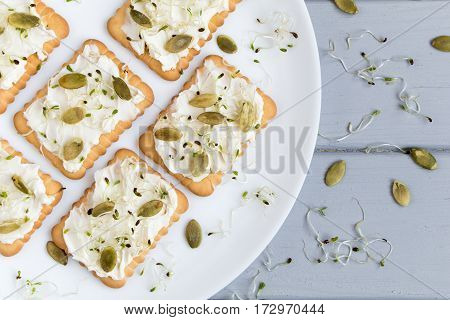 Tasty square crackers with cream cheese pumpkin seeds and micro greens. Appetizers on a plate on grey table. Healthy vegetarian snacks top view flat lay