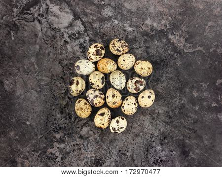 Decorative bright group of quail eggs on dark stone background. Flat lay top view natural minimalist still life