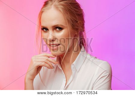 Photo of young pretty lady dressed in white shirt standing and posing over pink background. Looking at camera.