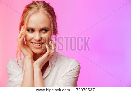 Image of young amazing lady dressed in white shirt standing and posing over pink background. Looking aside.