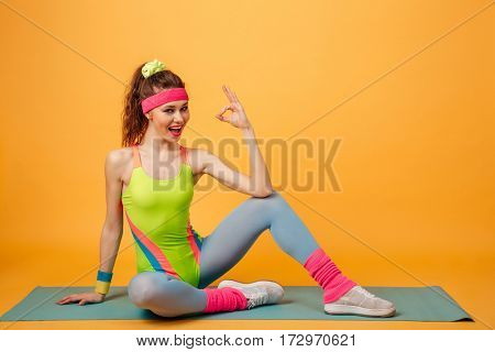 Happy cute young sportswoman sitting on mat and showing ok gesture