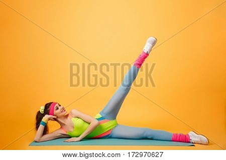 Smiling beautiful young fitness woman lying and exercising on mat over yellow background