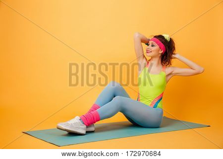 Cheerful pretty young woman athlete training and working out on mat over yellow background