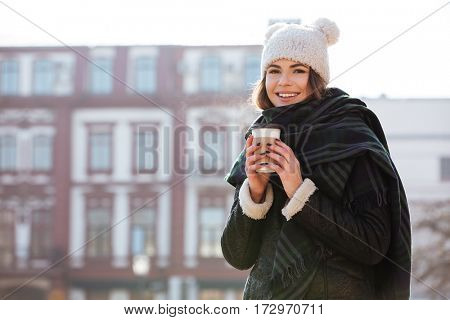 Smiling attractive young woman drinking coffee to go in the city