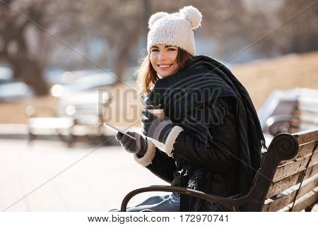 Happy attractive young woman drinking coffee and using cell phone on the bench in park