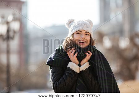 Happy beautiful young woman in funny hat and scarf standing outdoors