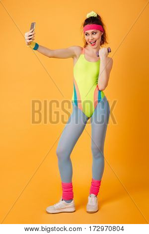 Full length of happy young fitness woman with dumbbells taking selfie using cell phone