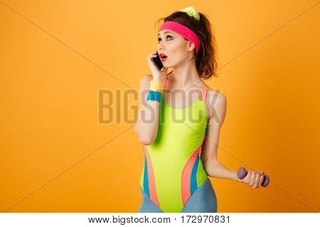 Beautiful young woman athlete exercising with dumbbells and talking on cell phone