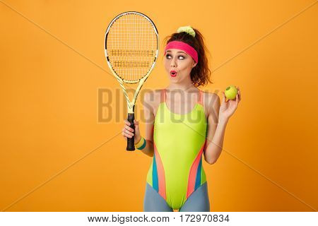 Cute amazed young fitness woman standing and holding tennis racket and ball