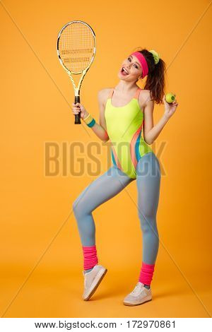 Full length of cheerful young fitness woman holding tennis racket and ball