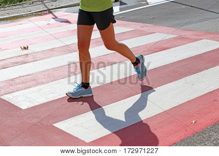 marathoner runs fast over the pedestrian crossing in the city during the sports competition